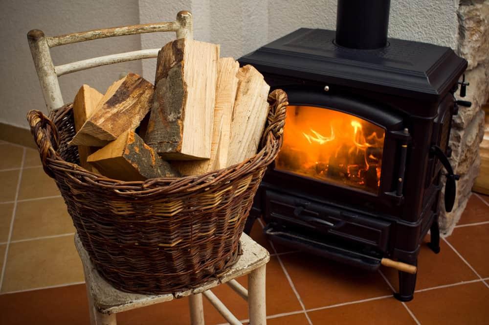 Holzkorb gefüllt vor einem Kamin