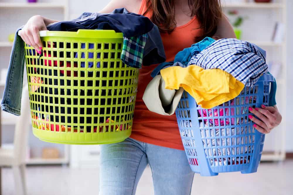 Frau trägt volle Wäschekörbe unsortierter Wäsche, da hilft ein Wäschesortierer