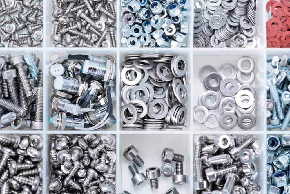 Verschiedene Schrauben, Unterlegscheiben und Muttern aus Metall in einer Sortierbox aus Kunststoff