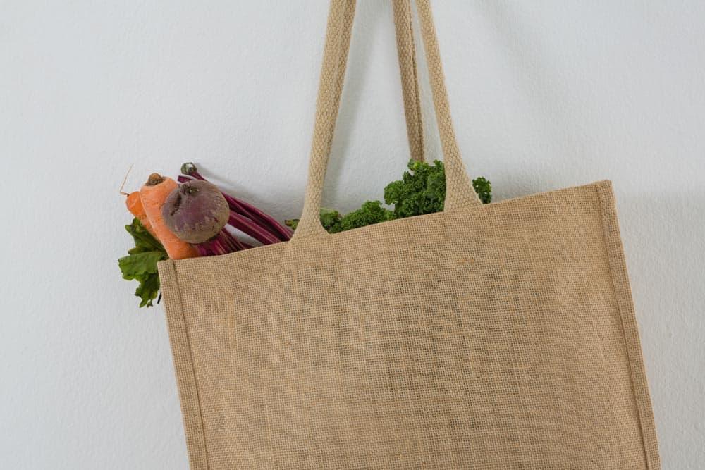 Jutesack mit Gemüse vor weißer Wand