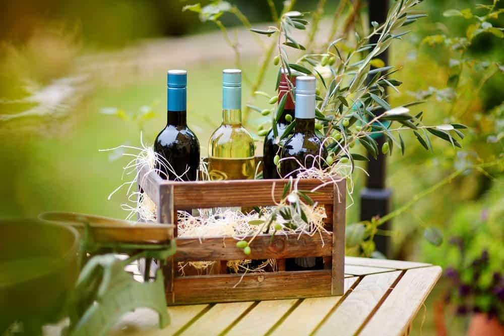 Drei Weinflaschen stehend in einer dekorativen Weinkiste