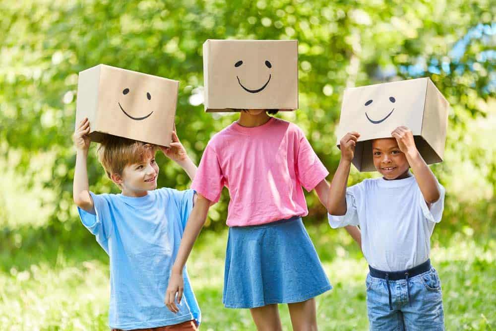 drei Kinder mit Pappschachteln auf dem Kopf