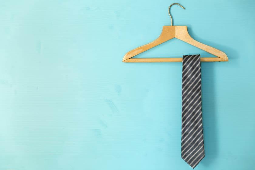 Krawatte Aufbewahrung: Krawatte auf Bügel vor blauem Hintergrund